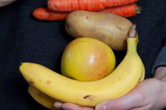 Banane, Apfel, Kartoffel und Möhren gestapelt auf einer Hand.