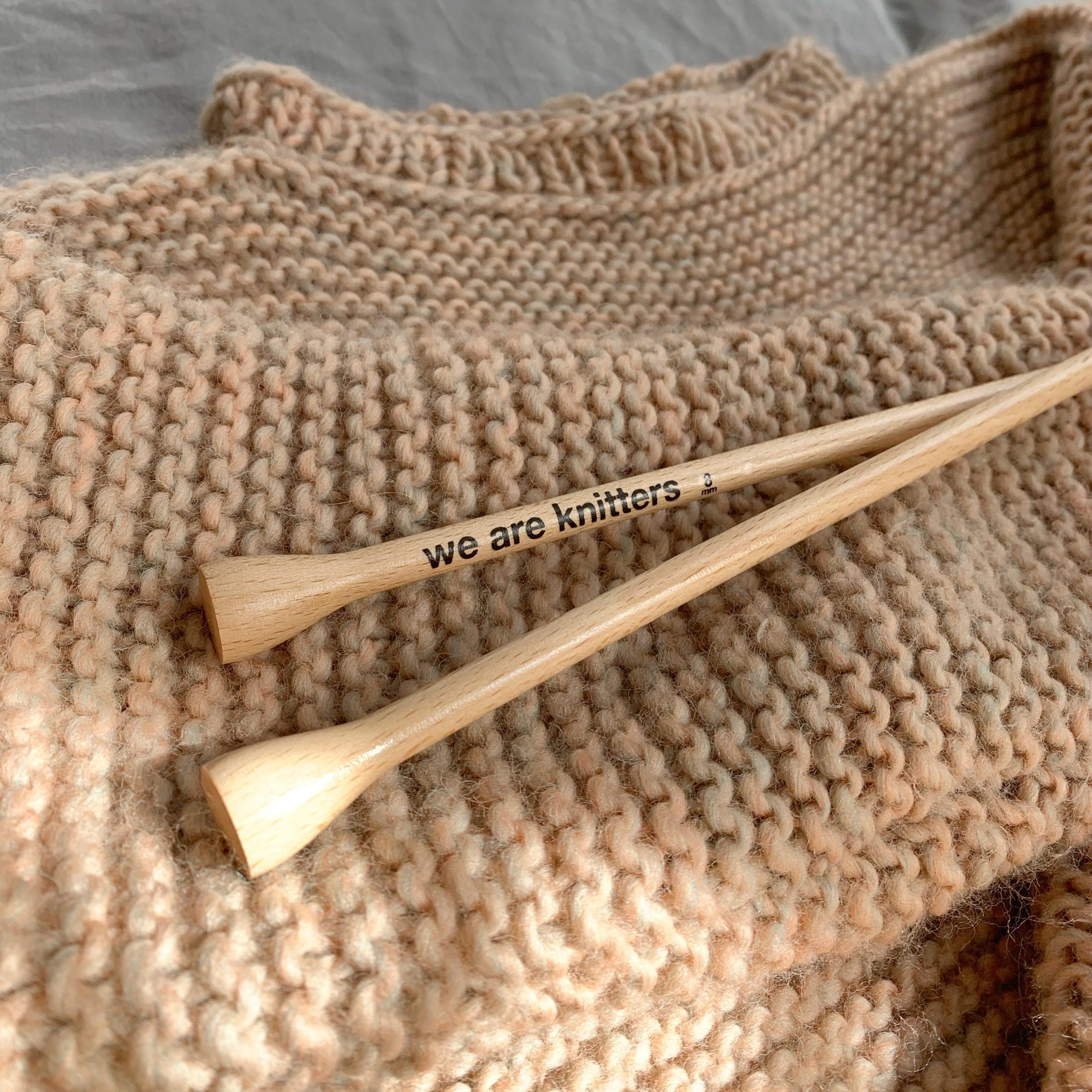 Ausschnitt eines Strickpullovers in Altrosa mit Bambus-Stricknadeln